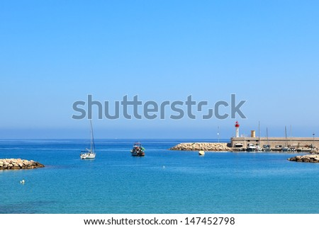 View of yachts and boats floating on calm surface of Mediterranean sea at the entrance to marina in Menton, France.