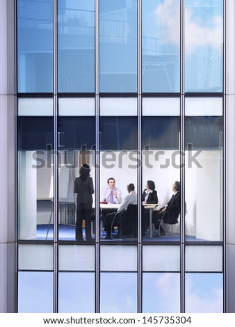 View of young businessman with colleagues in meeting room through window - stock photo