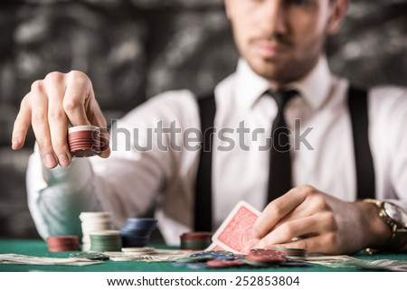View of young, confident, gangster man in shirt, suspenders and hat, while he's playing poker game. - stock photo