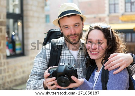 View of Young couple of tourist watching photographs on camera