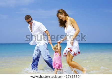 view of young family having fun on the beach - stock photo