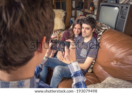 View of young friend taking photos with a smartphone to hipster teenage couple sitting in the sofa