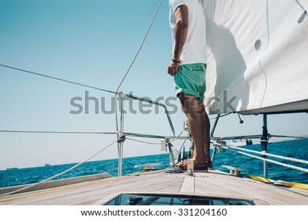 View of young man standing on the nose yacht - stock photo