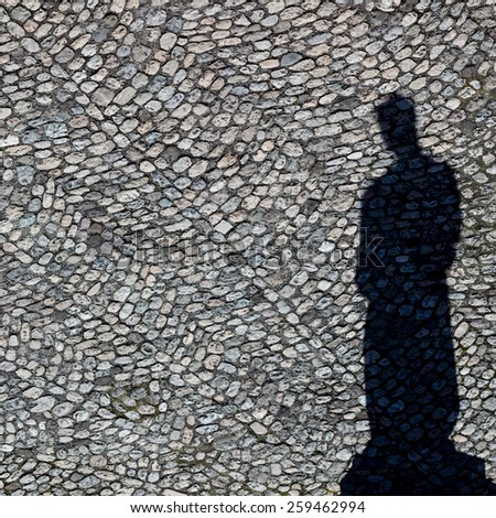 View on a shadow of a statue on cobblestones  - stock photo
