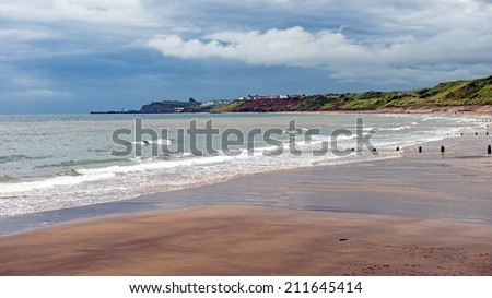 View on a threatening cloudy day along the North Yorkshire coast beach from Sandsend to Whitby, England showing the harbor entrance and abbey ruins  - stock photo