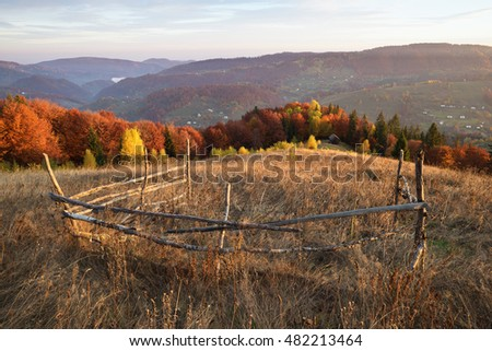 View on a wooden house in a mountain village. Wooden fence in the meadow with dry grass. Beautiful deciduous forest on the hill. Sunny weather. Carpathians, Ukraine, Europe