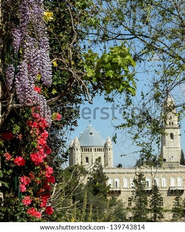 View on Abbey of the Dormition in Jerusalem. Natural frame of colorful flowers and green leaves. - stock photo