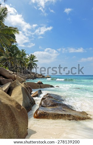 View on an untouched tropical beach with palm trees and rocks, turquoise ocean, clear blue sky, Seychelles islands - stock photo