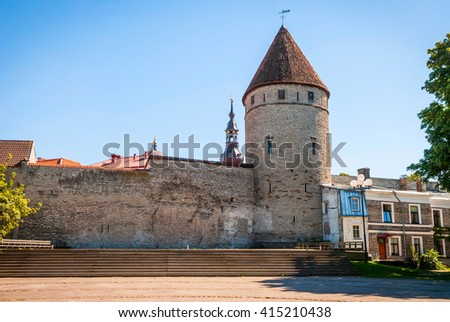 View on ancient street with medieval tower and wall of Tallinn, Estonia - stock photo