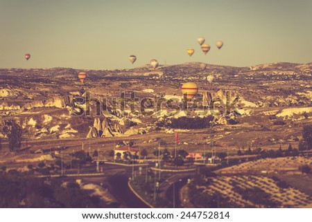 View on balloons fly over Cappadocia  with tilt shift lens effect . Goreme National Park. Urgup, Goreme, Guzelyurt and Uchisar. Turkey. Filtered image:cross processed vintage effect.  - stock photo
