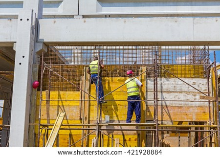 View on building site until workers are assembly a huge mold with reinforcement mesh for concreting. - stock photo