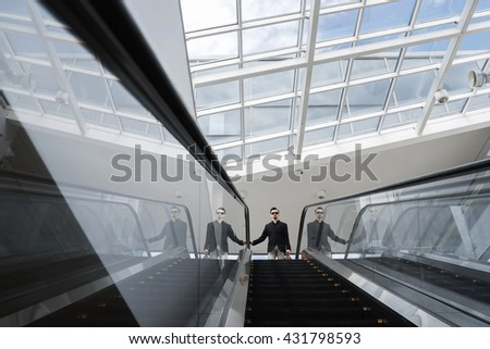 View on businessman in sunglasses standing on top of stairway