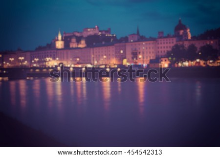View on city, far hills, mountains. Blue night sky. Summer. Walk evening on curve river. Vintage photo. Poster, Bokeh background, Salzburg, Austria, Europe. evening lights city. Spain, France, Italy