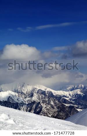 View on cloudy mountains and off-piste slope. Caucasus Mountains, Georgia, ski resort Gudauri. - stock photo