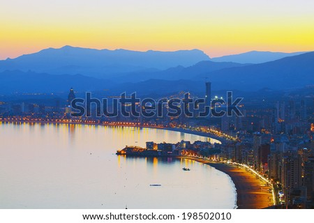 View on evening city with a sea beach on a background of mountains in the mist (Spain, Benidorm) - stock photo