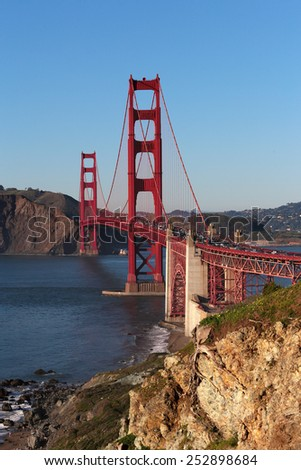 View on Golden Gate suspension bridge which link San Francisco with northern bay aria by road in evening light looking north with blue sky, water shoreline rocks and traffic on the bridge - stock photo