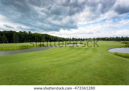 View on golf course at cold day with rainy clouds on sky