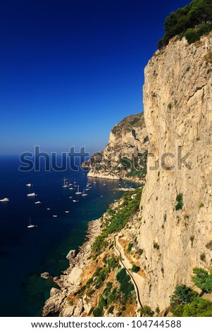 view on great steep cliff on Capri island with blue water - stock photo
