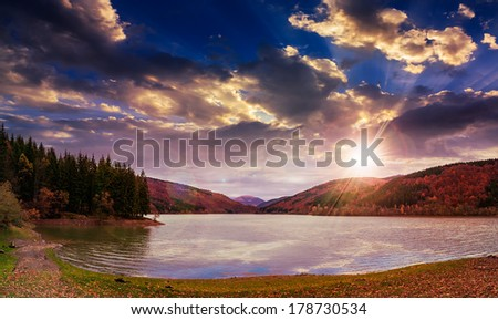 view on lake near the pine forest at sunset on mountain background - stock photo