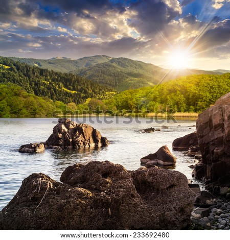 view on lake with rocky shore and some boulders near forest on mountain  with high vista far away in sunset light - stock photo