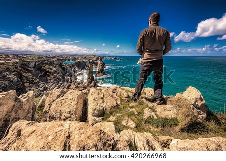 View on man standing on top of the mountain overlooking dramatic view of  Playa de la Arnia, rocky coastline in Santander ,Cantabria, Spain. - stock photo