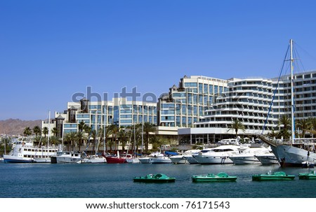 View on marina and docked yachts and boats in popular resort and recreation center of Israel - Eilat city - stock photo