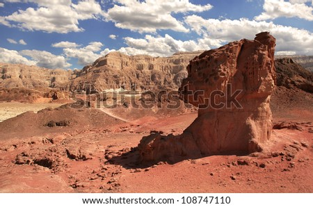 View on mushroom shaped red rock and mountains on background at Timna National Park in Arava Desert, Israel.