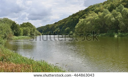 View on of river with water ripple, autumn mountain forest under cloudy sky at sanatorium  region Tovtry in Ukraine