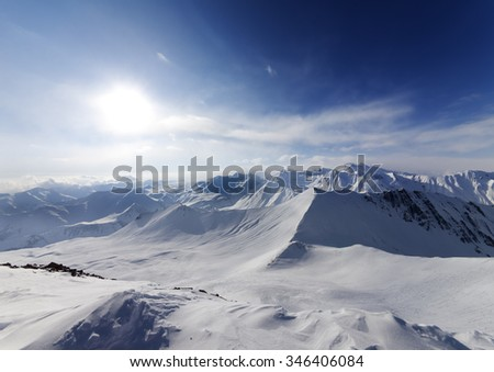 View on off-piste slope and sky with sun. Caucasus Mountains, Georgia, ski resort Gudauri. Wide angle view. - stock photo