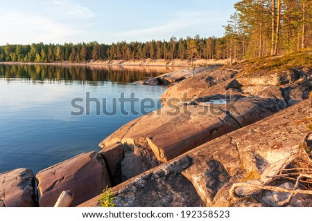 View on Onega Lake bay granite shore with pine forest at midnight sun. Besov Nos cape, Karelia Republic, Russia.