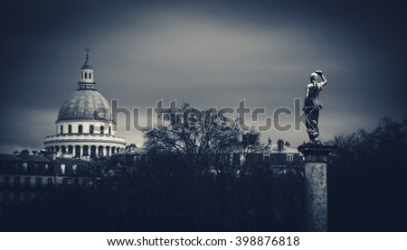 View on Pantheon building from Luxembourg gardens in cloudy day. Selective focus on the statue. Toned evening photo with vignette effect. - stock photo