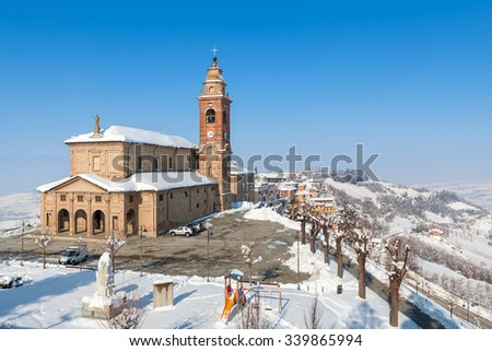 View on parish church and snowy hills of Piedmont, Northern Italy. - stock photo