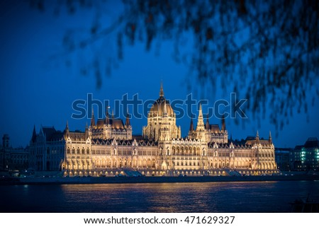 View on parliament building from Buda part of Budapest. Danube river in foreground, evening cloudy sky in background. Hungary, Europe travel.