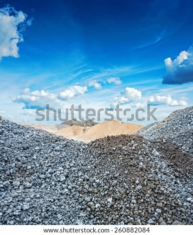 view on piles of gray granite gravel and construction sand  - stock photo