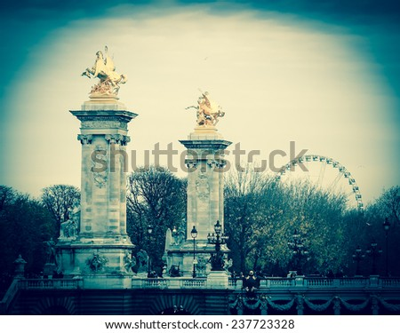 View on Pont Alexandre III (Alexander III Bridge) and ferris wheel at background in autumnal cloudy evening. Aged photo. Vignette. - stock photo