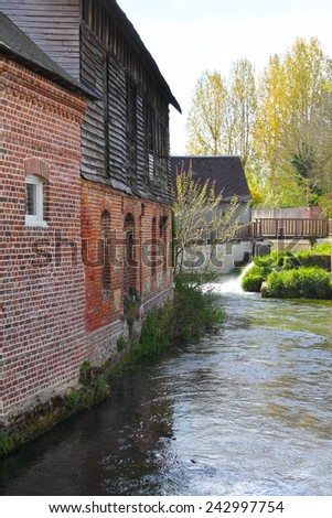 View on river and old houses in Auffay town, France - stock photo