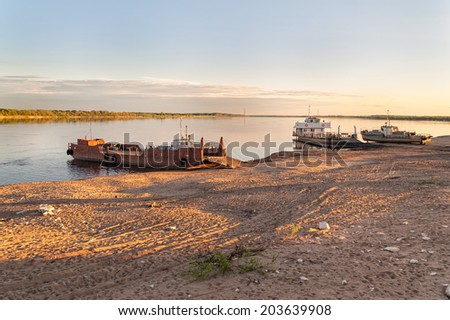 View on river with two ferryboats moored and old ship on sand beach at sunset. Solvychegodsk, Arkhangelsky region, Russia.  - stock photo