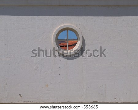View on rooftops trough a round window in a white wall. - stock photo