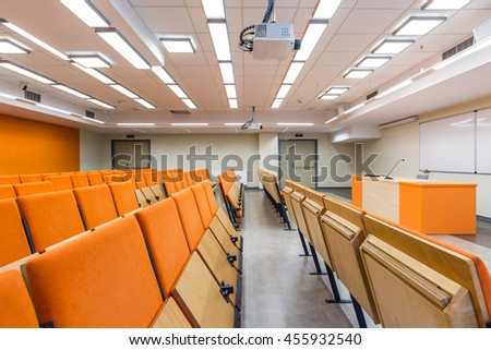 View on row of wooden chairs and lecturer desk in the lecture hall decorated with orange accents
