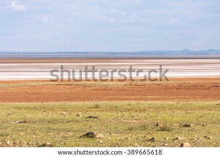 View on savanna plain before mountains against cloudy sky background. Lake Manyara National Park, Tanzania, Africa.