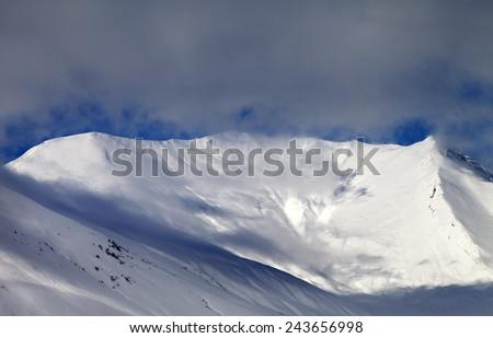 View on sunlight off-piste slope in mist. Caucasus Mountains, Georgia, ski resort Gudauri. - stock photo