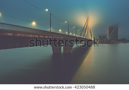 View on the cable bridge in Riga from embankment of Daugava river. Image toned for inspiration of retro style