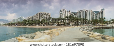 View on the central beach of Eilat from marine pier. Eilat is a famous tourist Israeli city with beautiful tropical beaches and resort hotels  - stock photo