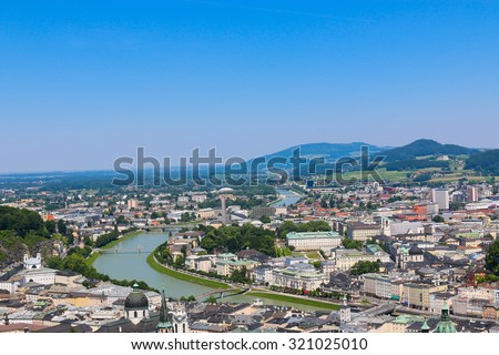 View on the city and far hills, mountains. Panoramic view of Salzburg skyline and river Salzach, Austria. Summer sunny day with blue clouds on sky. Kollegienkirche. Salzburger Dom. Vintage photo.  - stock photo