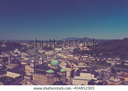 View on the city and far hills, mountains. Panoramic view of Salzburg skyline and river Salzach, Austria. Summer sunny day with blue clouds on sky. Kollegienkirche. Salzburger Dom. Vintage photo