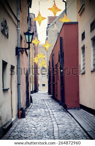 View on the narrowest street with decorative lamps, old Riga city, Latvia, Europe - stock photo
