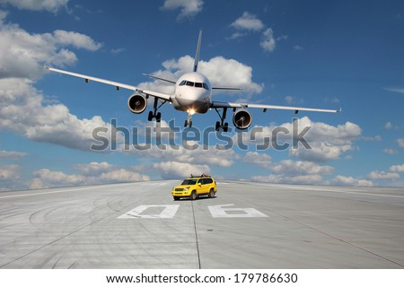 View on the threshold of runway 06 with follow me car and a passing plane - stock photo