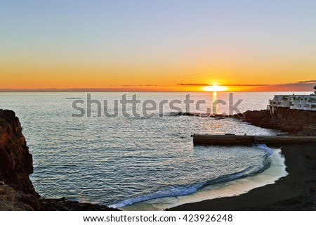 View on the volcanic sands beach in sunset time  in Tenerife, Canary Islands, Spain  - stock photo