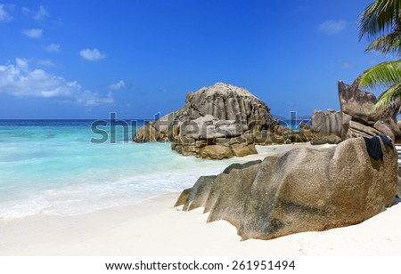 View on tropical white sand beach with turquoise ocean, granite rocks and palm trees, Seychelles islands - stock photo
