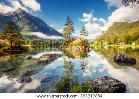 View on turquoise water and scene of trees on a rock island at Lake Hintersee. Location famous resort National park Berchtesgadener Land, Ramsau, Bavaria, Alps. Europe. Artistic picture. Beauty world. - stock photo